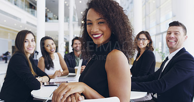 Buy stock photo Cropped shot of a young businesswoman smiling in an office during a meeting with her colleagues in the background