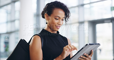 Buy stock photo Cropped shot of a young businesswoman using a digital tablet while walking through a modern office