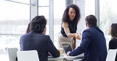 Buy stock photo Cropped shot of a businesswoman shaking hands with colleagues during a meeting in an office