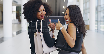 Buy stock photo Cropped shot of two young businesswomen giving you a thumbs up while walking in an office