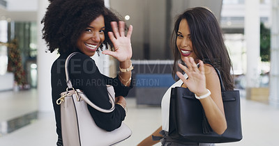 Buy stock photo Cropped shot of two young businesswomen waving while walking in an office
