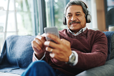 Buy stock photo Cropped shot of a mature man listening to music through his cellphone