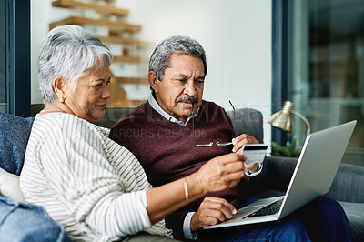 Buy stock photo Shot of a mature woman holding up a card while browsing with her husband online