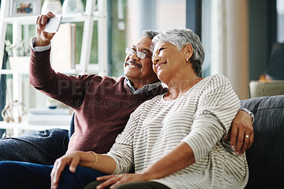 Buy stock photo Cropped shot of a happy mature couple taking a selfie while relaxing at home