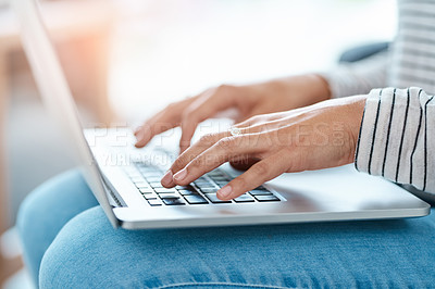 Buy stock photo Cropped shot of an unrecognizable young woman using her laptop at home