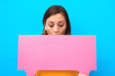 Buy stock photo Cropped shot of a young woman holding a speech bubble against a blue background