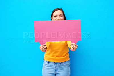 Buy stock photo Cropped portrait of a young woman holding a speech bubble against a blue background