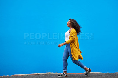 Buy stock photo Full length shot of an attractive young woman walking against a blue background