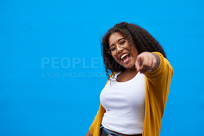 Buy stock photo Cropped portrait of an attractive young woman pointing against a blue background