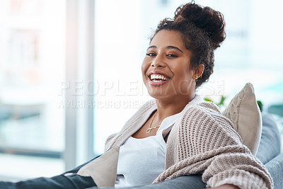 Buy stock photo Cropped portrait of a happy young woman relaxing on her couch at home