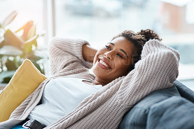 Buy stock photo Cropped portrait of an attractive young woman relaxing on her couch at home