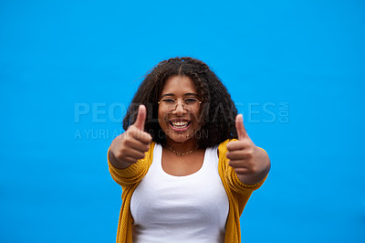 Buy stock photo Cropped portrait of an attractive young woman showing thumbs up against a blue background