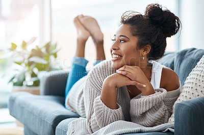 Buy stock photo Full length shot of a happy young woman relaxing on her couch at home
