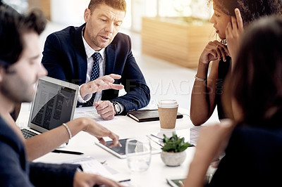 Buy stock photo Shot of a mature businessman having a meeting with his colleagues in an office