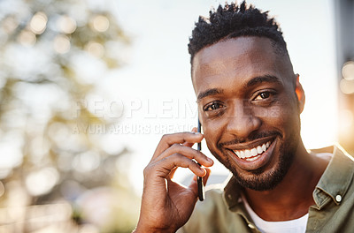 Buy stock photo Cropped portrait of a handsome young man using his cellphone while standing outside