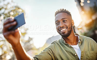 Buy stock photo Cropped shot of a handsome young man taking selfies while standing outside