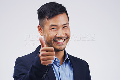 Buy stock photo Studio portrait of a handsome young businessman giving a thumbs up against a grey background