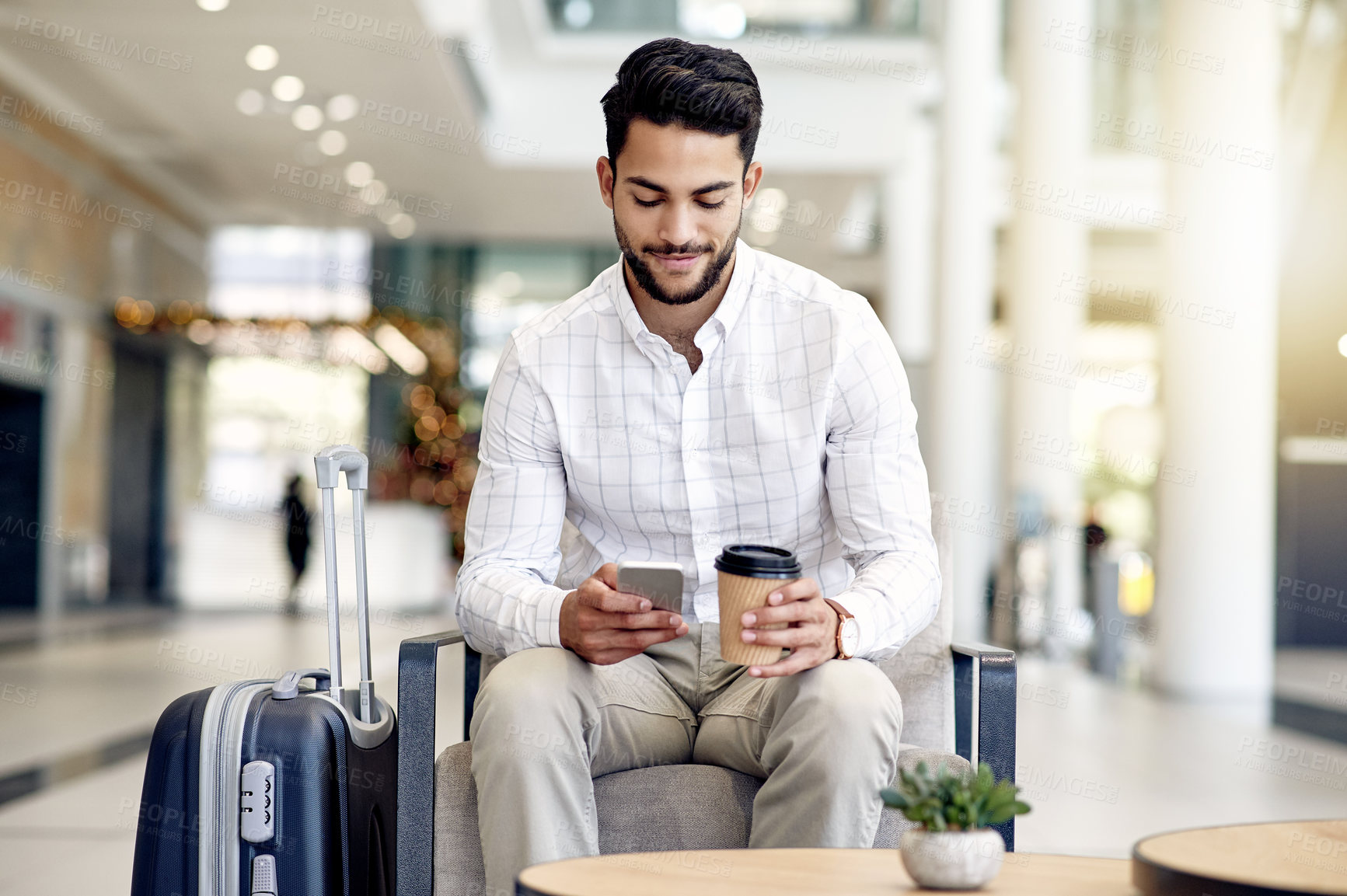 Buy stock photo Shot of a focused young businessman texting on his phone and drinking coffee while waiting for his flight at the airport