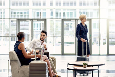 Buy stock photo Shot of two young businesspeople having a discussion while being seated inside of a busy airport