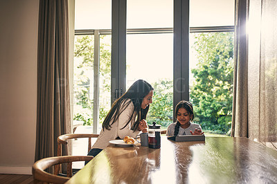 Buy stock photo Shot of a young woman using a digital tablet wth her daughter at home