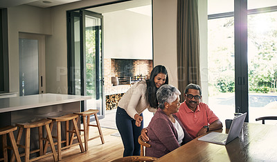 Buy stock photo Shot of a young woman using a laptop with her parents at home