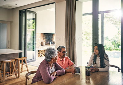 Buy stock photo Shot of a young woman chatting and having coffee with her parents at home
