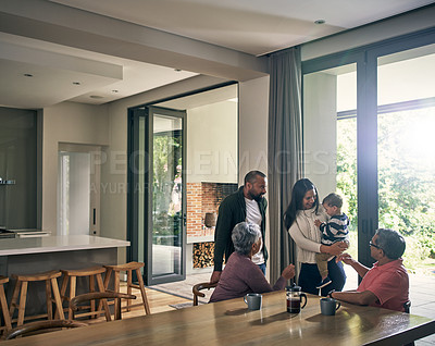 Buy stock photo Shot of a happy young family visiting their elderly parents at home