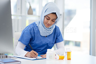 Buy stock photo Cropped short of an attractive young female doctor filling out paperwork while sitting in her office in the hospital