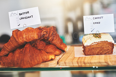 Buy stock photo Shot of carrot cake and croissants in a display case at a cafe