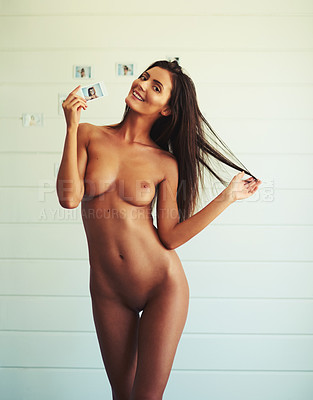 Buy stock photo Shot of an attractive young woman holding a camera while posing nude against a picture wall