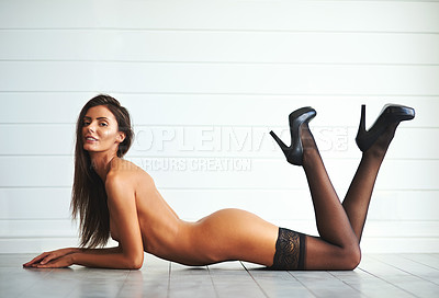 Buy stock photo Full length shot of an attractive young woman lying down on the floor and posing nude against a grey background