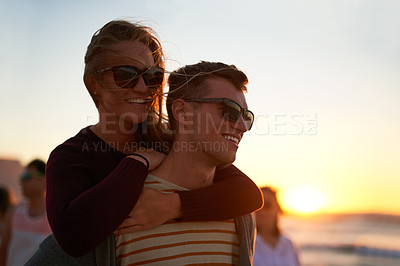 Buy stock photo Cropped shot of a young man piggybacking his girlfriend at the beach