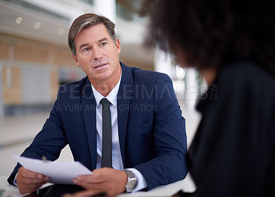 Buy stock photo Cropped shot of two businesspeople going over paperwork in the boardroom