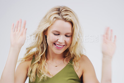 Buy stock photo Studio shot of an attractive young woman feeling cheerful and dancing against a grey background
