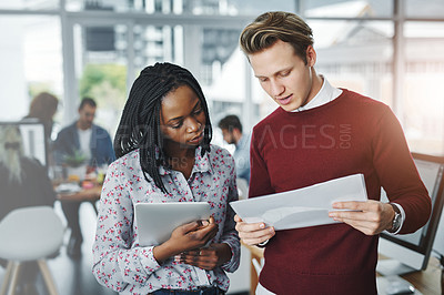 Buy stock photo Shot of two young colleagues discussing paperwork together in a modern office
