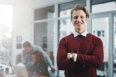 Buy stock photo Portrait of a confident young man with his colleagues in the background at work
