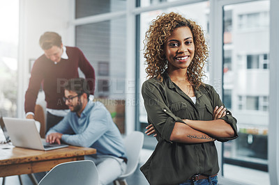 Buy stock photo Portrait of a confident young woman with her colleagues in the background at work