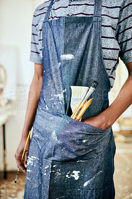 Buy stock photo Shot of a young male artist working in his studio