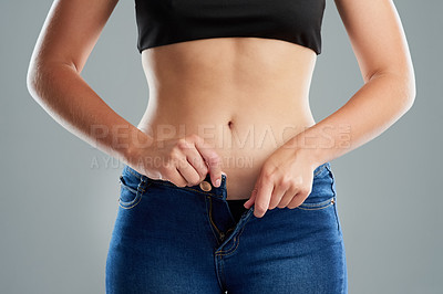 Buy stock photo Studio shot of an unrecognizable woman buttoning her jeans against a grey background