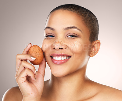 Buy stock photo Studio shot of a beautiful young woman holding a egg against her face