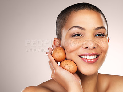 Buy stock photo Studio shot of a beautiful young woman holding eggs against her face