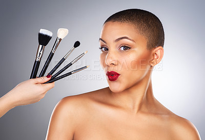 Buy stock photo Studio shot of a hand holding makeup brushes next to a beautiful young woman's face