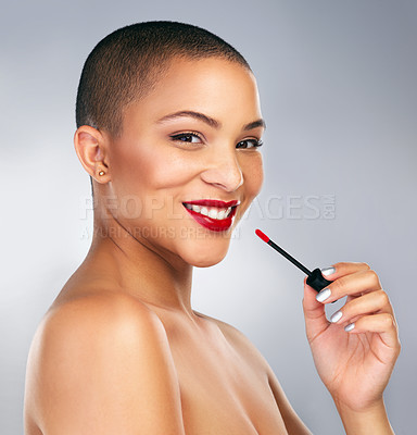 Buy stock photo Studio shot of a beautiful young woman applying red lipstick against a grey background