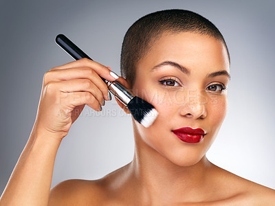 Buy stock photo Studio shot of a beautiful young woman applying makeup against a grey background