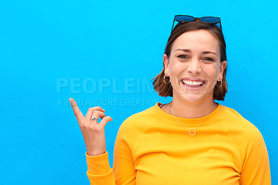 Buy stock photo Cropped portrait of a happy young woman pointing up against a blue background