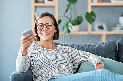 Buy stock photo Cropped shot of a happy young woman using the remote control on the sofa at home