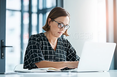 Buy stock photo Cropped shot of a focused young businesswoman working on a laptop in an office