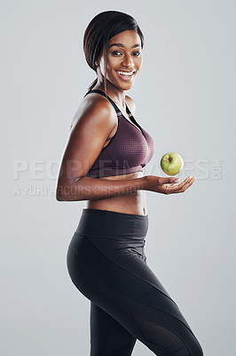 Buy stock photo Studio portrait of an attractive and fit young woman posing with an apple in her hand against a grey background