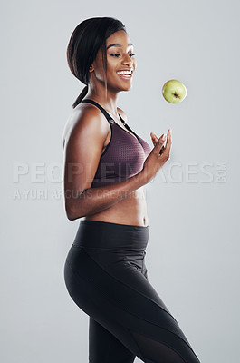 Buy stock photo Studio shot of an attractive and fit young woman throwing an apple in the air against a grey background