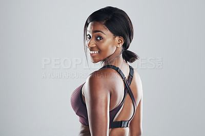 Buy stock photo Studio portrait of an attractive and fit young woman posing against a grey background